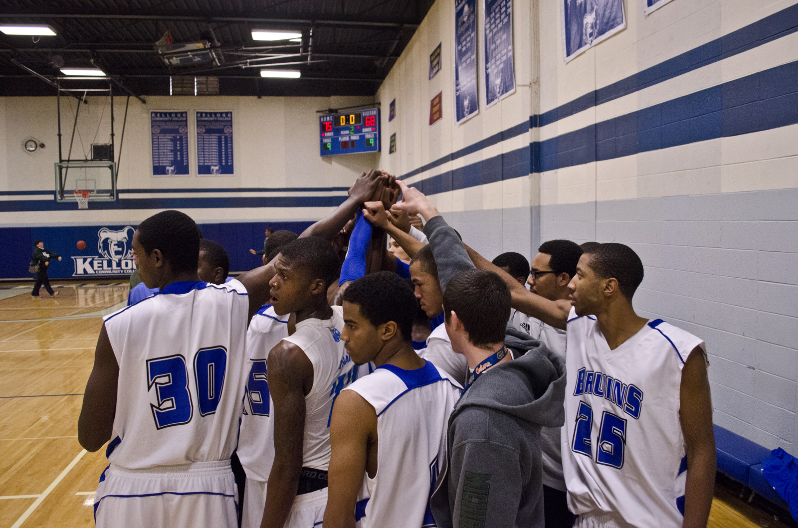 Members of KCC's men's basketball team join hands in a huddle during a game at the Miller Gym