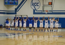 The women's basketball team holds hands over their heads in the Miller Gym before a home game.