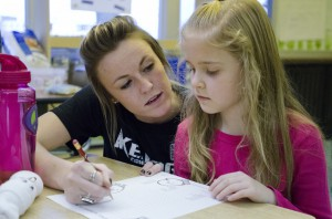 Mackenzie Kendall, 19, a centerfielder studying early childhood special education at KCC, helps a second grader with a worksheet.