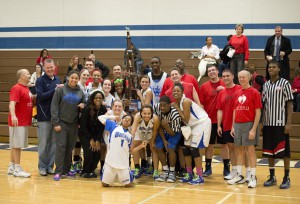 Participants in the Hoops for Heart charity basketball game pose following the game.