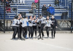 Softball players celebrate a run at home plate