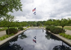 An American flag flying over the reflecting pools on KCC's North Avenue campus.
