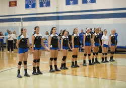 KCC's women's volleyball stands on the court holding hands during the National Anthem before a match.