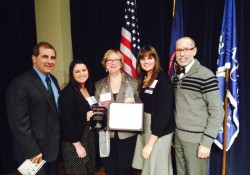 KCC professor Glenda Morling poses with her Lifetime Achievement Award from Michigan Campus Compact with KCC officials.