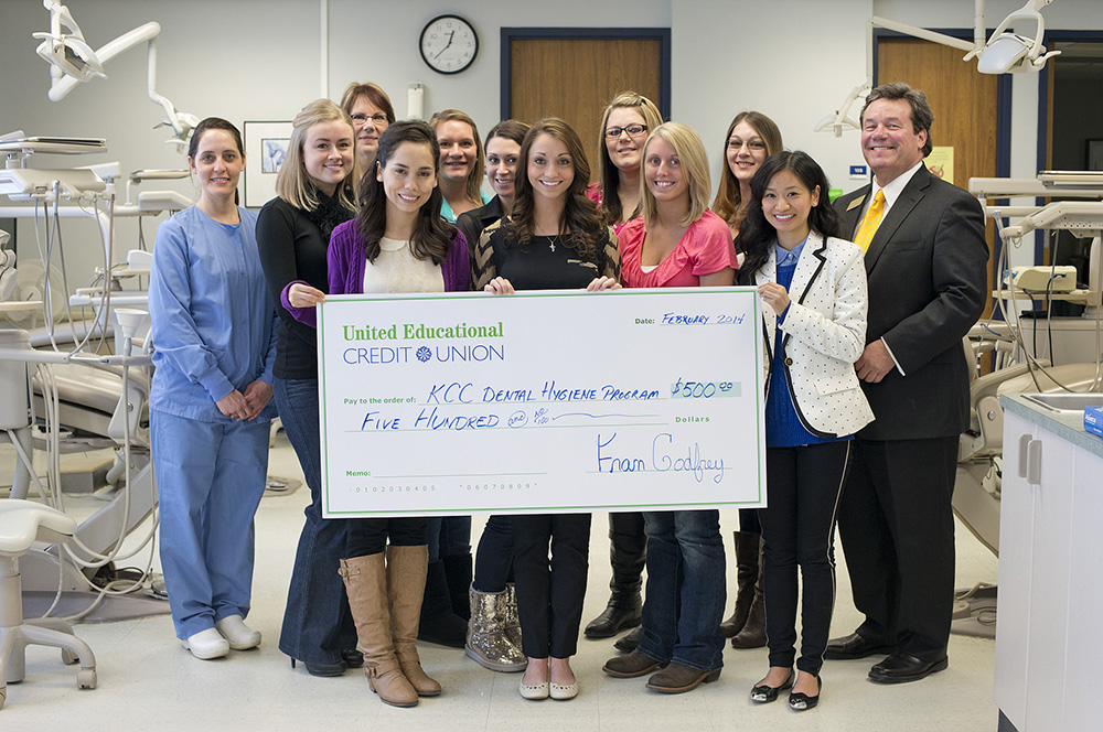 Dental Hygiene students pose with a check presented by United Educational Credit Union's Scott White