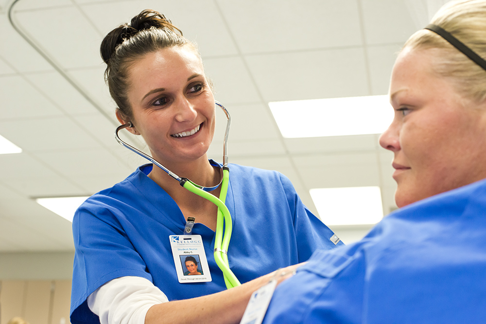 A KCC Nursing student works on another student during class
