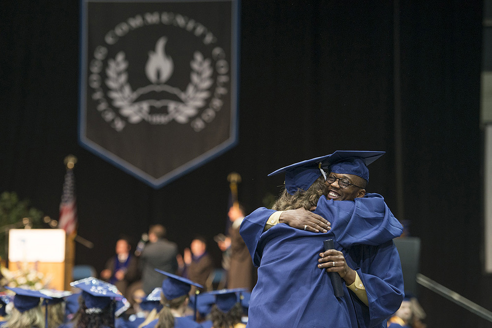 Graduates hug during KCC's 2014 commencement ceremony.