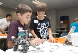 Students work on a robot during a camp at the RMTC.