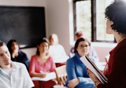 A stock photo of students listening to an instructor in class.