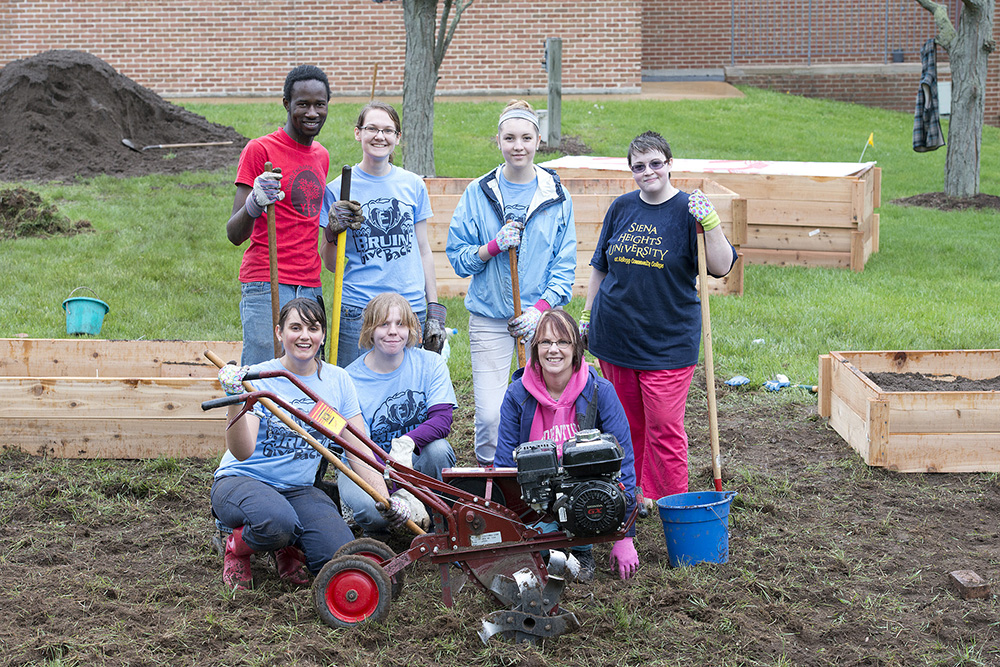 KCC students and employees pose while working in KCC's community garden.