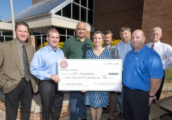 Members of a local IBEW present a donation check to KCC and KCC Foundation officials outside on campus.