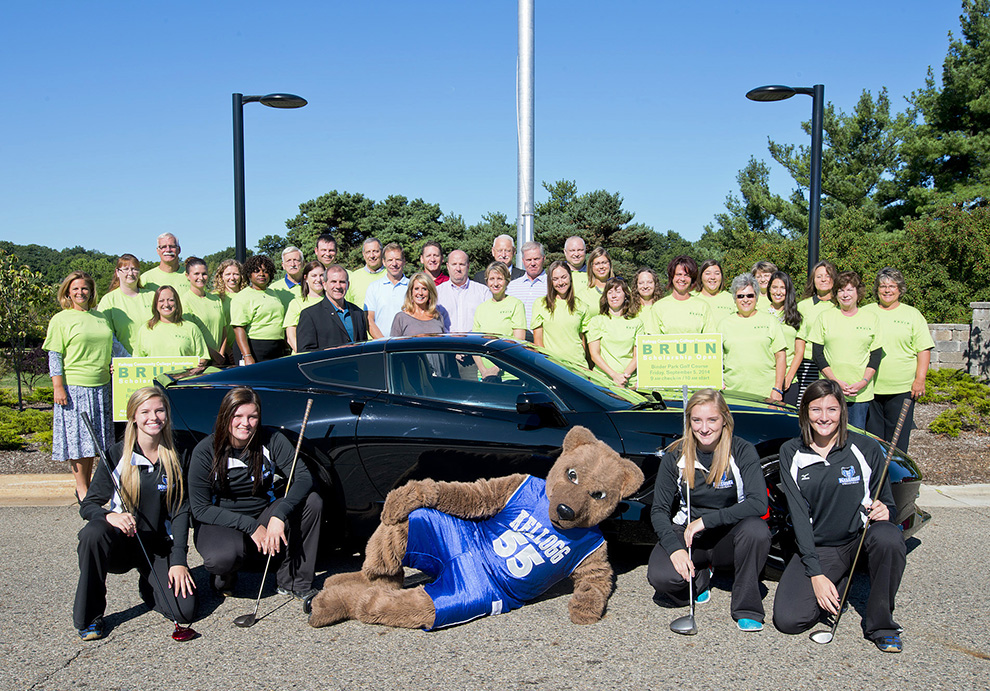 KCC Foundation Bruin Scholarship Open volunteers pose for a group photo with a car in front of the North Avenue campus.