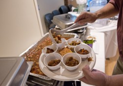 A photo of a patron at KCC's 2013 Chili Cook-Off filling a cup on his plate with chili.