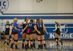 Women's volleyball players celebrate after scoring a point during a match at the Miller Gym.