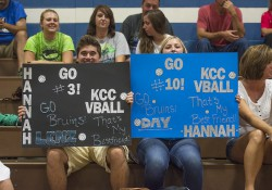 Volleyball team supporters hold signs during a home match.