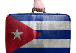 Tourist hand holding vintage travel bag with flag of Cuba