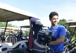 A KCC baseball player volunteers securing golf bags during the 2014 Bruin Scholarship Open.