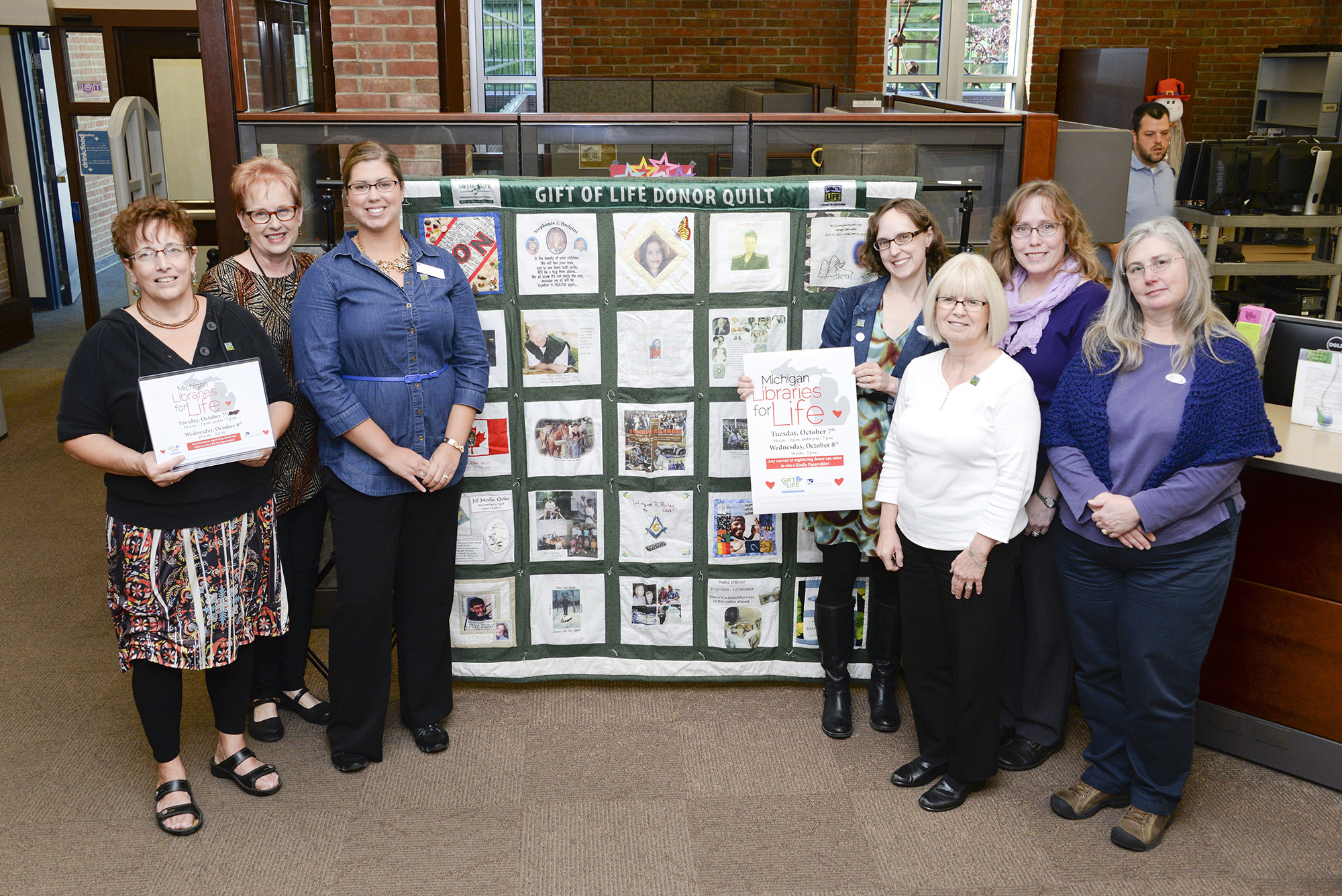 Library staff pose with an organ donor quilt in the library following an organ donation information event at KCC.