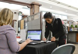 A student registers for a chance to win a Kindle at the Michigan Libraries for Life table in the KCC library.