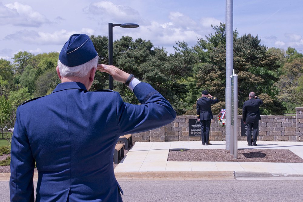 A KCC employee and veteran salutes during a Memorial Day ceremony outside on campus.