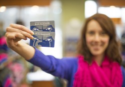 A Bruin Bookstore employee holds up two bookstore gift cards.