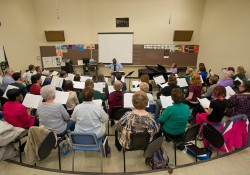 Members of KCC choirs rehearse in a music room.