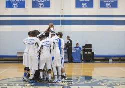 Members of the men's basketball team huddle on the court before a home game at the Miller Gym.