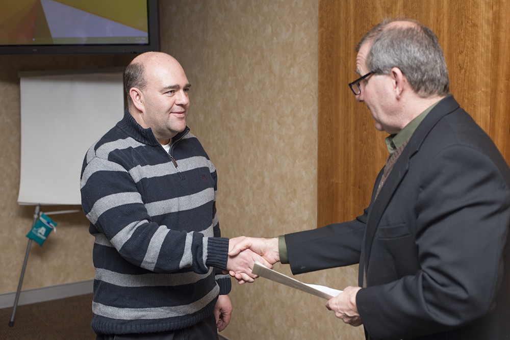 New KCC board member Patrick O'Donnell shakes hands with KCC President Dr. Dennis Bona after swearing in during a board meeting.