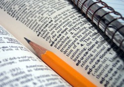 Stock photo of a pencil and notebook laying in a dictionary opened to the entry on education.