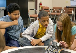 Two young boys and a girl work with a robot during a youth robotics camp at KCC's RMTC.