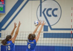 KCC women's volleyball players block the ball during a home game at the Miller Gym.