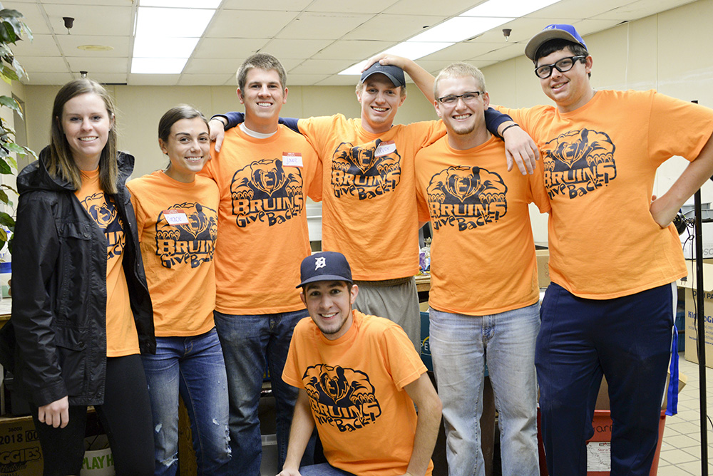 Student participants in Bruins Give Back pose while serving at a site off campus.