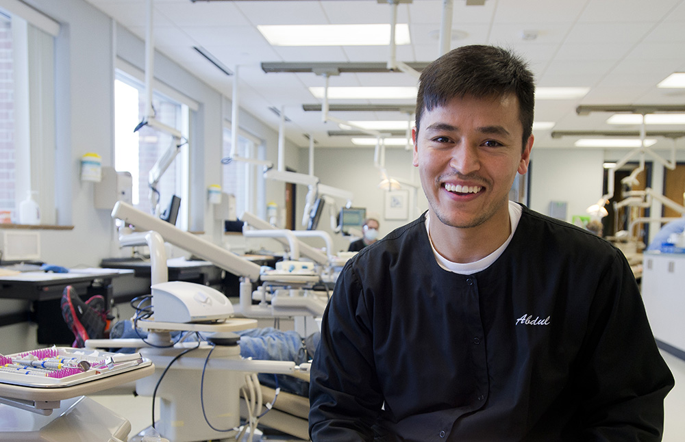 A male dental hygiene student poses in the KCC Dental Hygiene Clinic