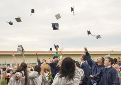 Calhoun Community High School graduates throw their caps in the air to celebrate following their commencement ceremony in 2013. Photo by Nick Garrison.