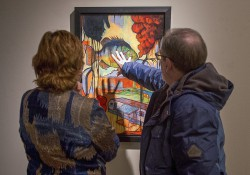 Exhibit goers look at a painting at the KCC Faculty Biennial Art Exhibition in February at the Art Center of Battle Creek.