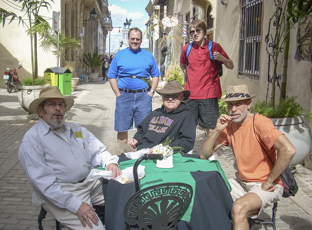 Members of the group that traveled to Cuba with KCC in February pose at a table between two buildings in a city there.