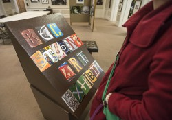 "A styled ""KCC Student Art Exhibit"" sign on a podium at the entrance to the exhibit at the Art Center of Battle Creek."