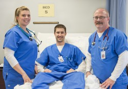 Three nursing students pose in a nursing lab.