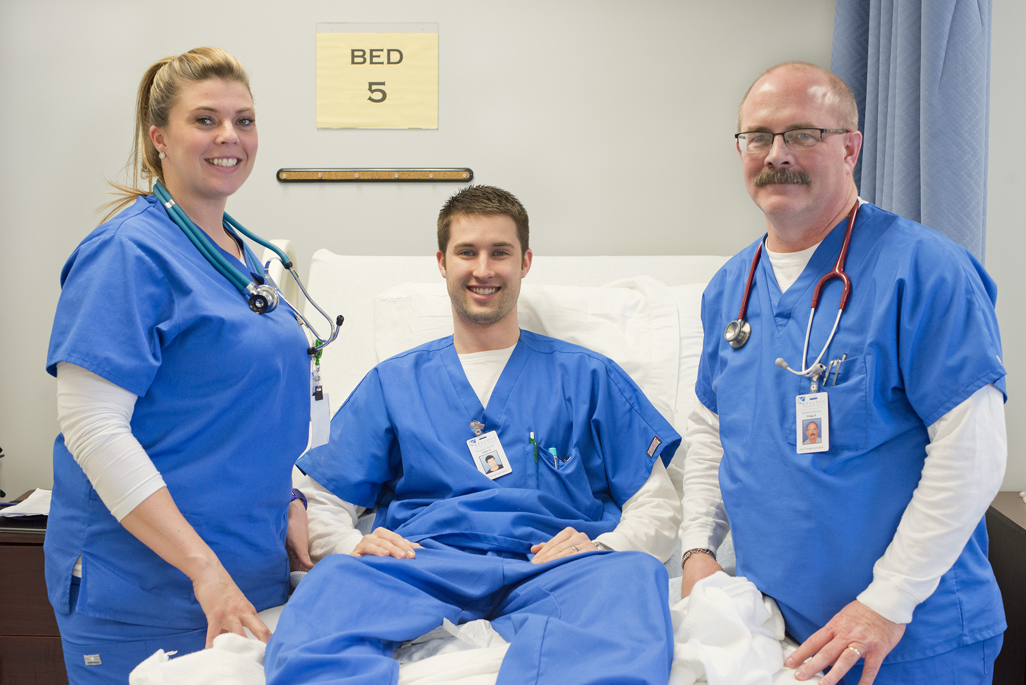 Three nursing students pose in a nursing lab.