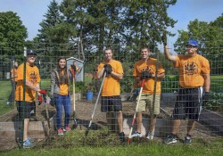 Student participants in Bruins Give Back pose while serving in KCC's community garden.