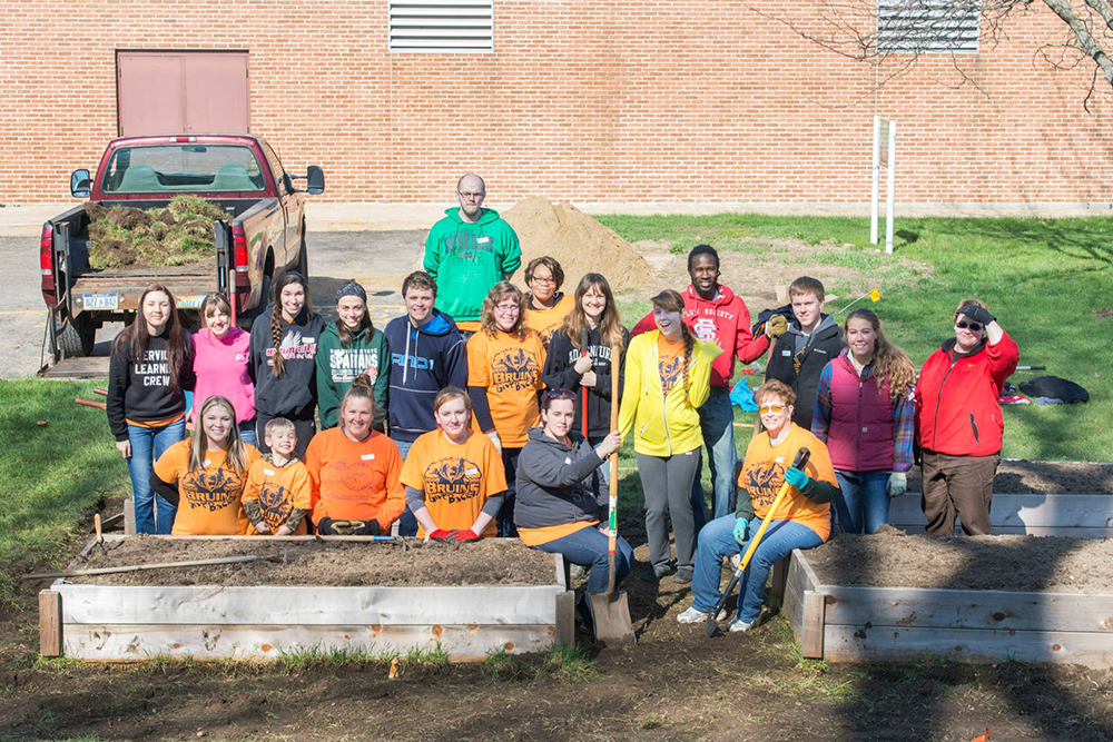 Volunteers pose for a group photo while working in KCC's community garden during a Bruins Give Back volunteer event.