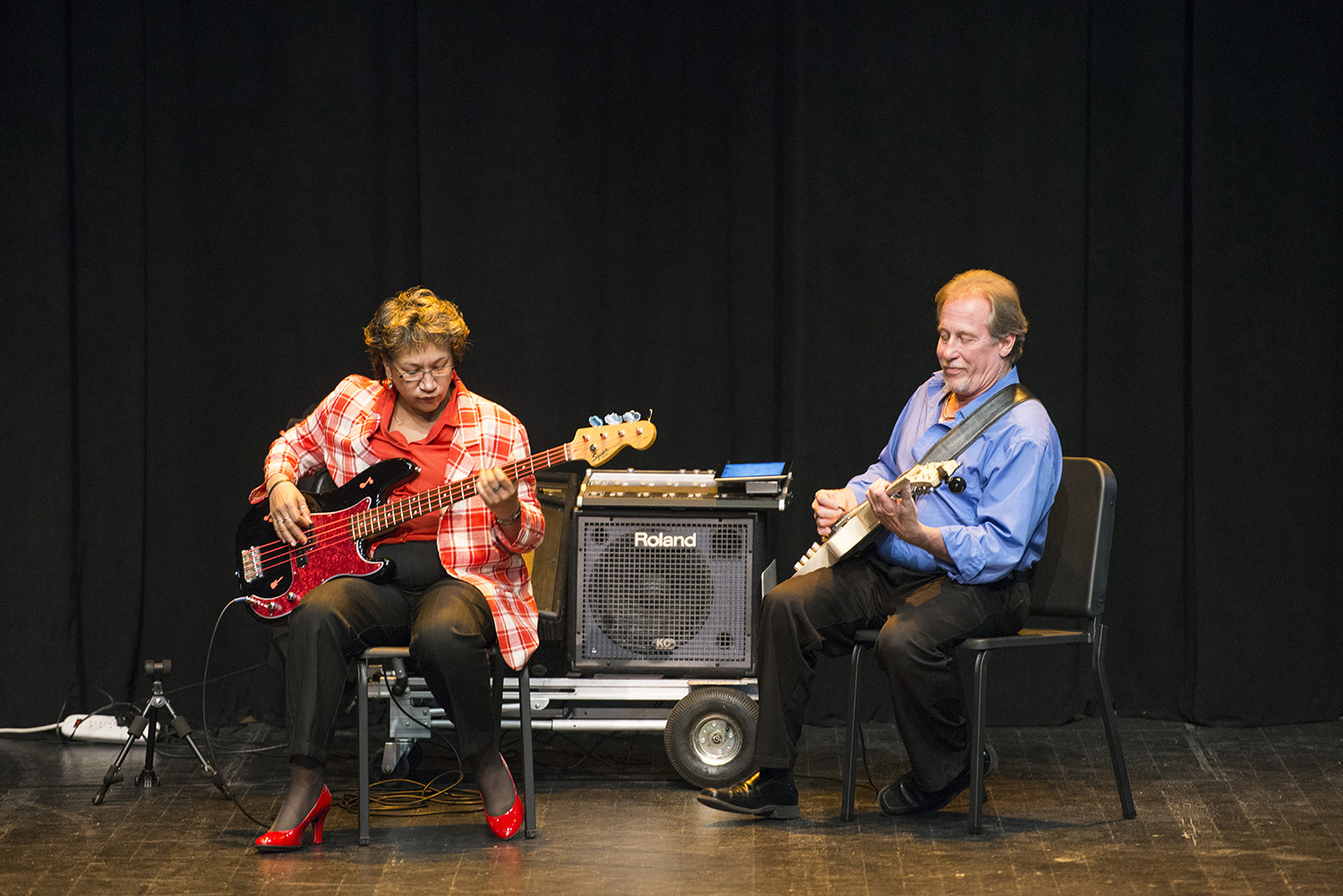 A female music student performs onstage with a guitar with instructor Paul Freeburn, also on guitar.