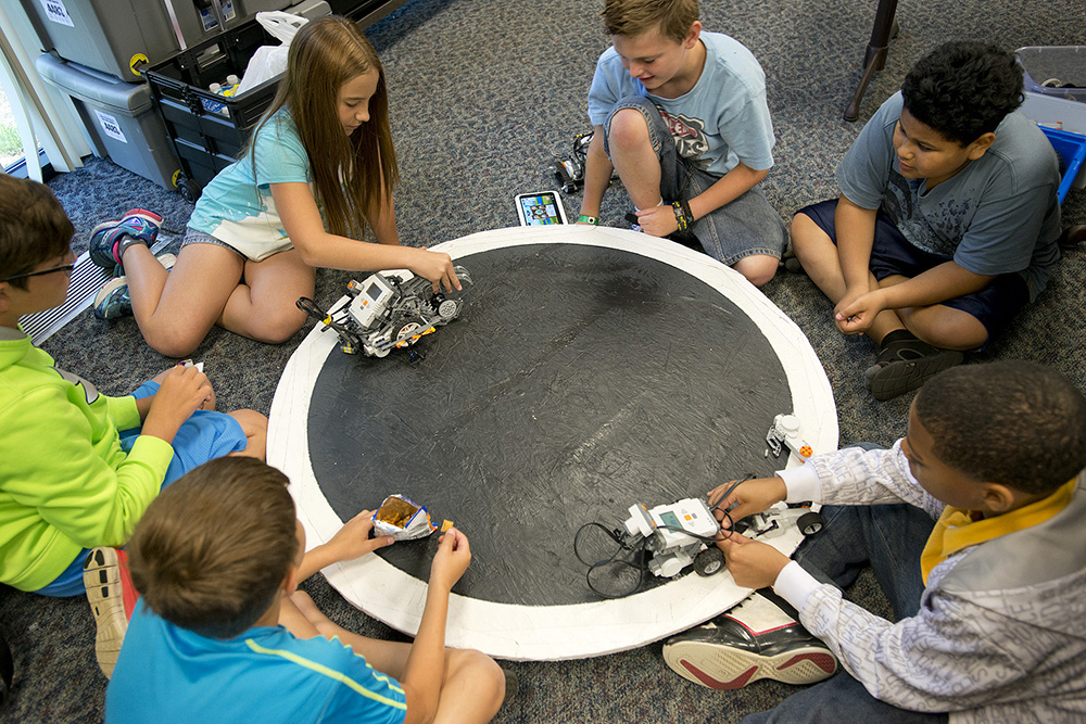 "Youth robotics campers prepare robots for a ""sumo"" battle on a round board during a KCC Robotics Camp at the RMTC."
