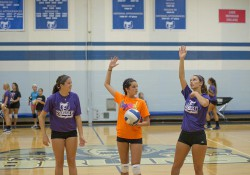 Two KCC volleyball players instruct a youth camper in the Miller Gym during a volleyball camp