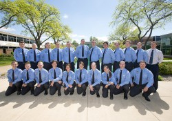 A group photo of KCC's 2014-15 Police Academy cadets, taken outside between the reflecting pools on the North Avenue campus in Battle Creek.