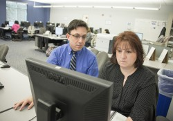An instructor assists a student with work on a computer in a KCC computer lab.