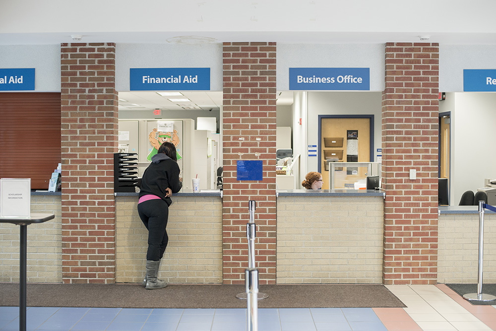 A student waits at the Financial Aid window on campus.