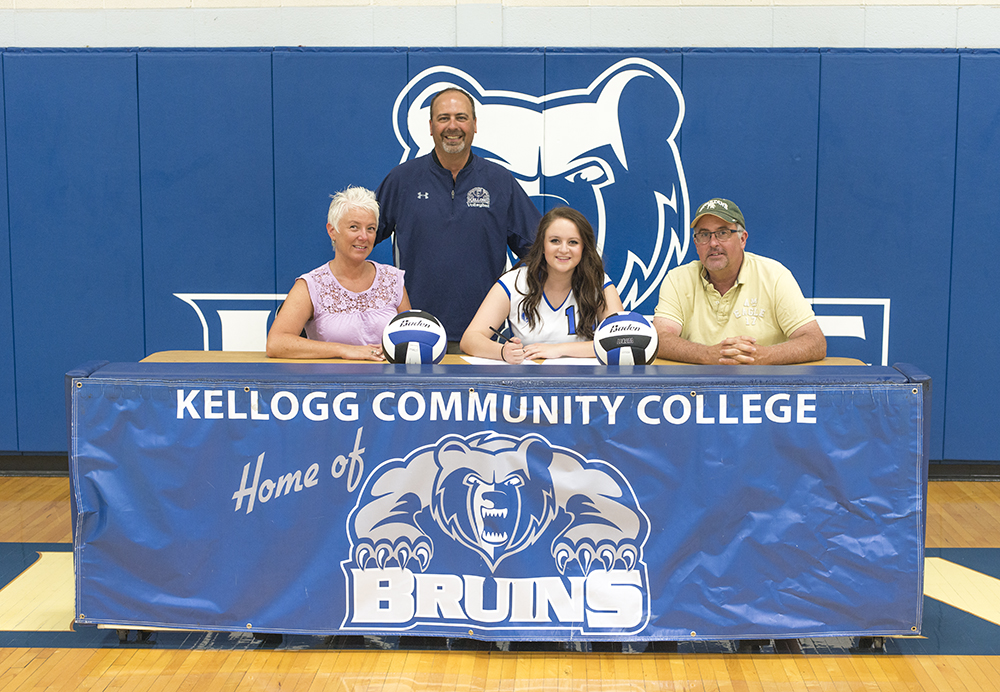 Miranda McDonald signs her National Letter of Intent to play women's volleyball for KCC, seated between her parents and in front of the team's coach.