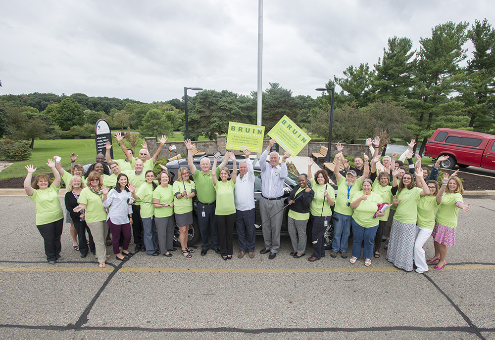 Bruin Open sponsors and KCC staff volunteering at the event pose for a group photo outdoors on campus in Battle Creek.