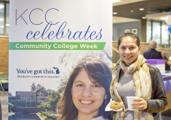 A student poses next to a community college poster featuring a photo of her